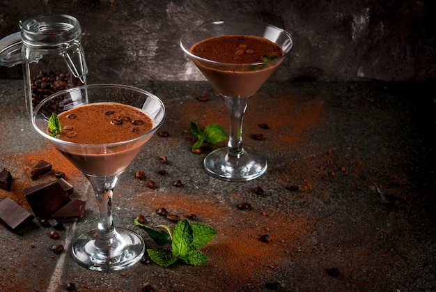 Cream coffee cocktail, chocolate martini with mint on black stone table
