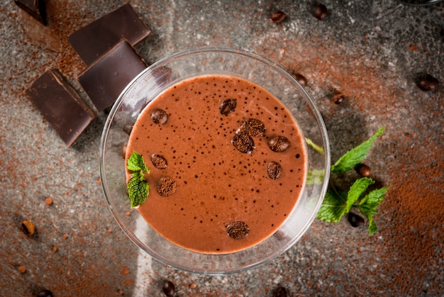 Коктейль из сливочного кофе, шоколадный мартини с мятой на черном каменном столе, вид сверху copyspace