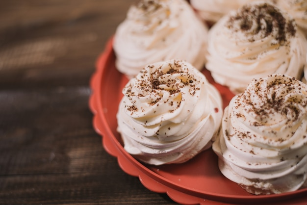Cream-colored pavlova meringue lies on a red tray on a wooden old table. chocolate coated meringue sweets recipe