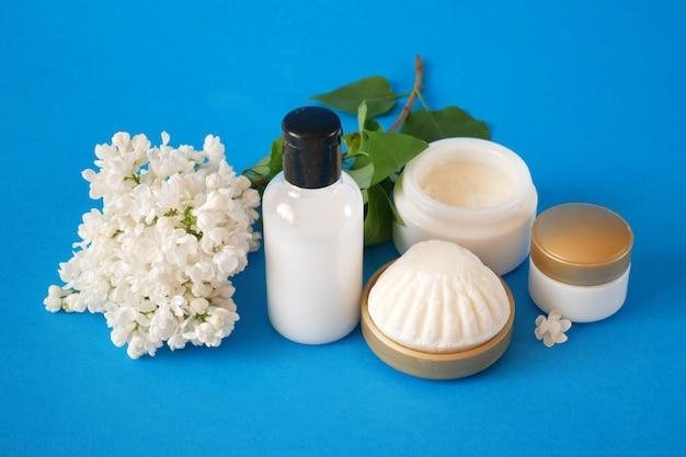 보라색 배경에 꽃과 라일락 화장품 세트 크림 화장품 비누와 추출물