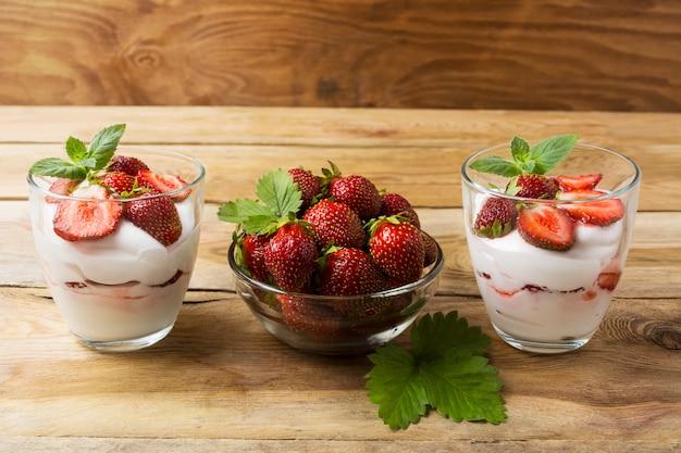 Cream dessert with strawberries on dark wooden