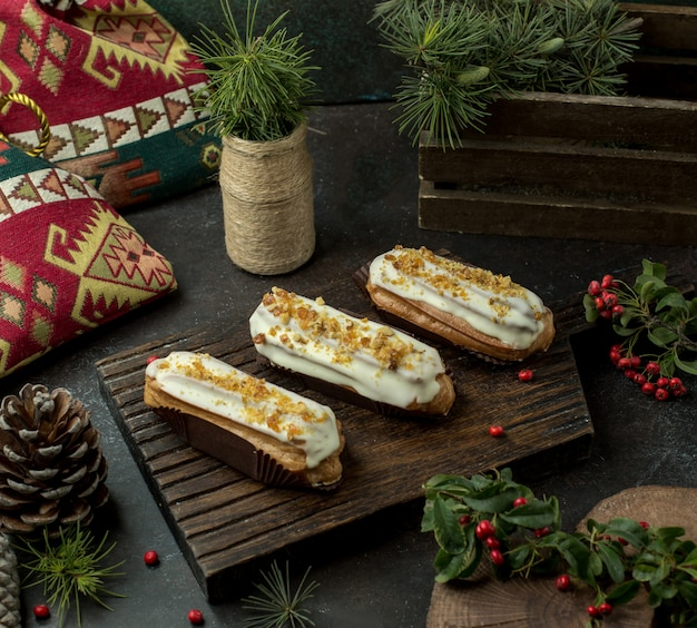 Cream eclairs on wooden board