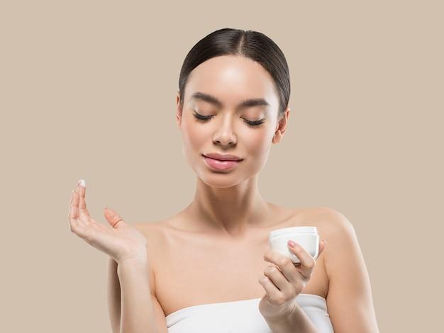 クリーム色の顔の女性の化粧品の健康的なスキンケアの美しさの肖像画を白で隔離色背景茶色