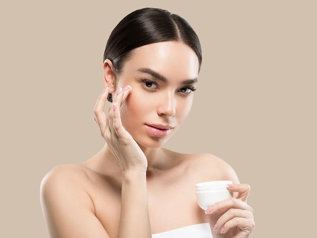 クリーム色の顔の女性化粧品健康的なスキンケアの美しさの肖像画を白で隔離色背景茶色