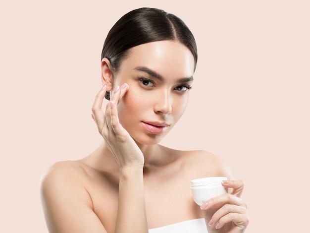 クリーム色の顔の女性化粧品健康的なスキンケアの美しさの肖像画を白で隔離色背景ピンク