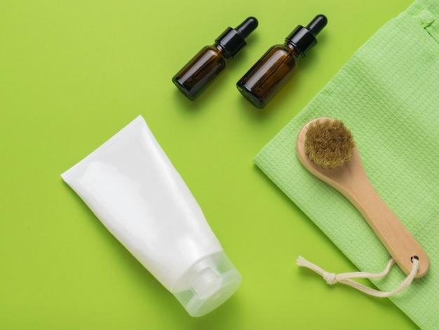 Крем, массажер для лица и две бутылки на зеленом фоне. спа. плоская планировка.