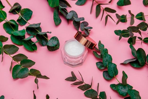 銀行のスキンケア用クリームは、ピンクのテーブルの上、ユーカリの葉と枝の周りにあります
