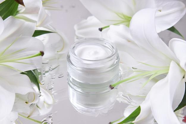 Крем для ухода за кожей, натуральная косметика из цветов и лепестков. стеклянная банка белого крема стоит среди цветов лилии.