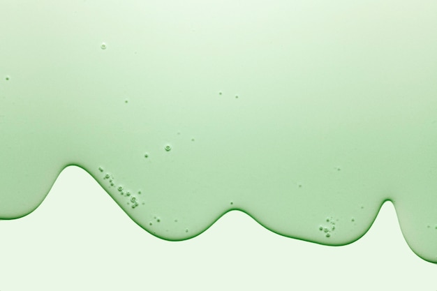 Cream gel green transparent cosmetic sample texture with bubbles isolated on green background