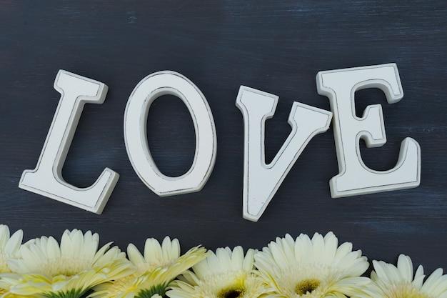 クリーム色のガーベラの花がラブレターでダークウッドに縁取られています
