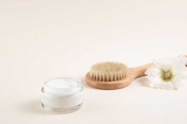 Cream and hair brush layout with plain background