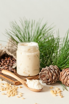 Cream honey with pine nuts. on a gray background. nearby pine nuts and cones. space for text and labels.