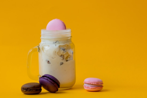 Cream ice cream with macarons in glass cup on yellow