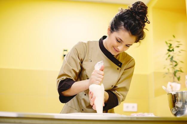 絞り袋にクリームを入れます。ベーキングツールを持つ女性。