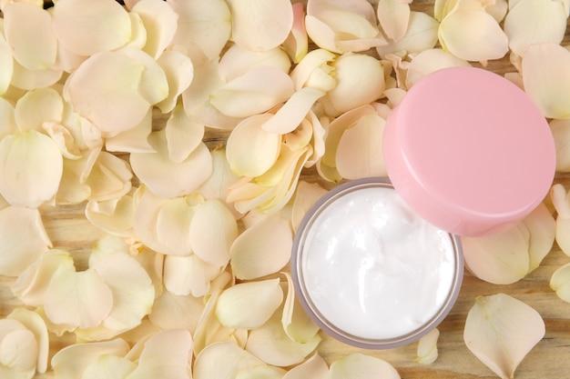 장미 꽃잎에 크림. 신선한 장미와 분홍색 병에 얼굴과 몸을위한 화장품. 온천. 텍스트를 놓습니다. 평면도