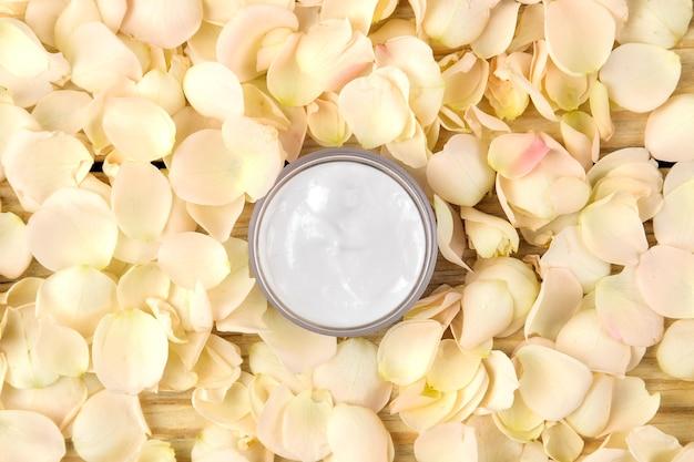 장미 꽃잎에 크림. 신선한 장미와 분홍색 병에 얼굴과 몸을위한 화장품. 온천. 평면도