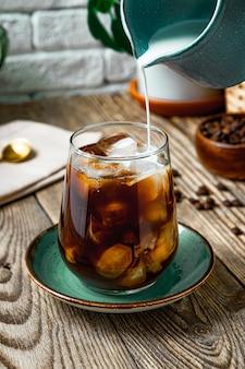 Сливки наливаются в стакан с холодным кофе, фото вертикальное. фото высокого качества
