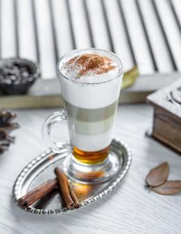 Cream milky cocktail with cinnamon powder.