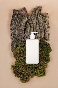 Cream, moisturizing lotion, shampoo or other cosmetic product in white blank bottle with dispenser on green moss and tree bark background.