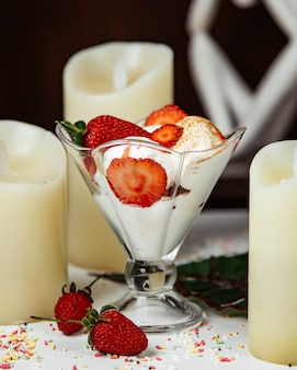 Cream mousse with strawberries around candles.