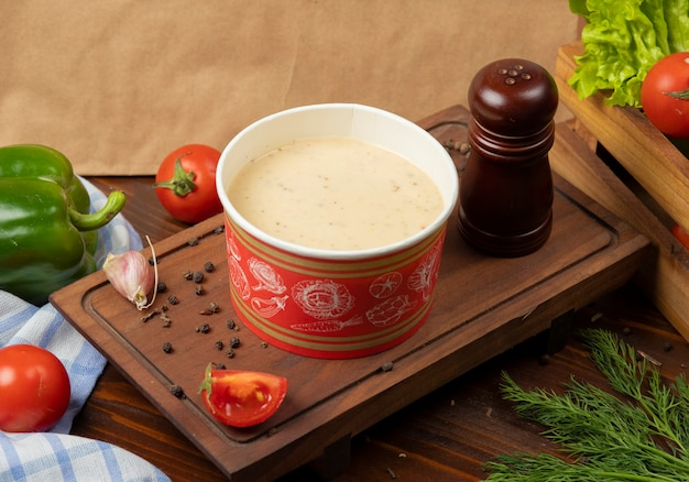 Cream mushroom soup in disposable cup bowl served with green vegetables.