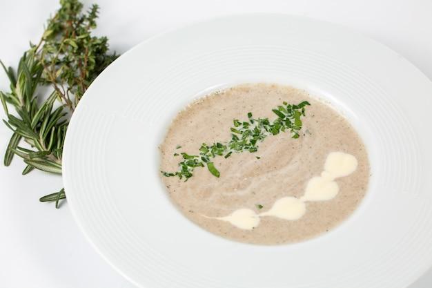 Zuppa di funghi crema in un piatto bianco su bianco