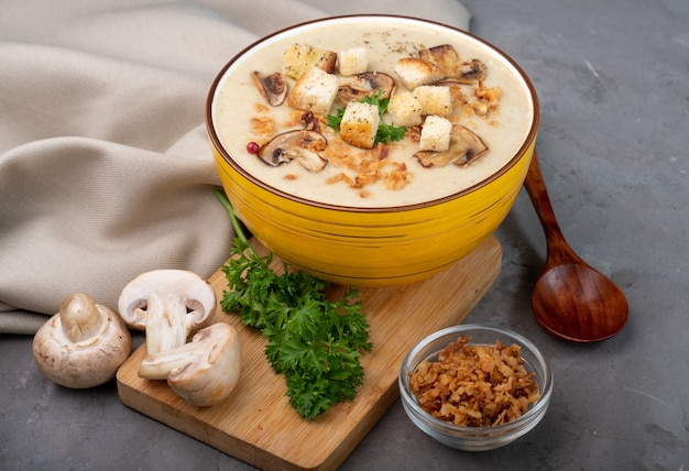 Cream of mushroom soup with cream with white bread croutons on a gray textured background.
