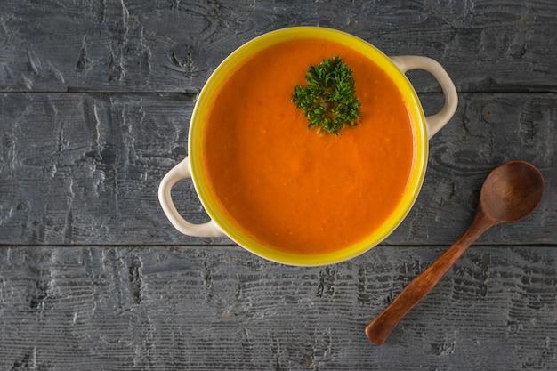 木のスプーンで唐辛子スープのクリーム。菜食のスープ。フラットレイ。上からの眺め。