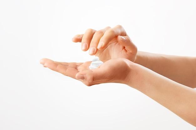 女性の手にクリーム。白い壁に隔離。健康な若い手。