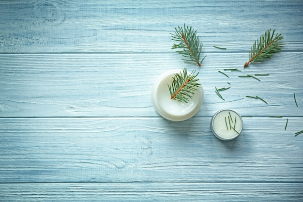 Cream and pine branches on wooden surface