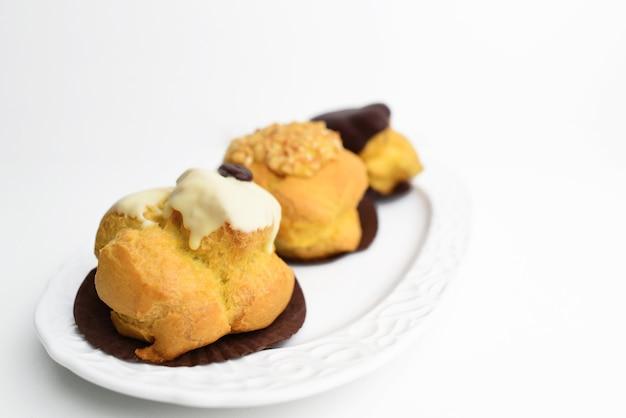 皿にシュークリーム。クリームとチョコレートソースのフレンチペストリー。イタリアの甘いプロフィットロール。
