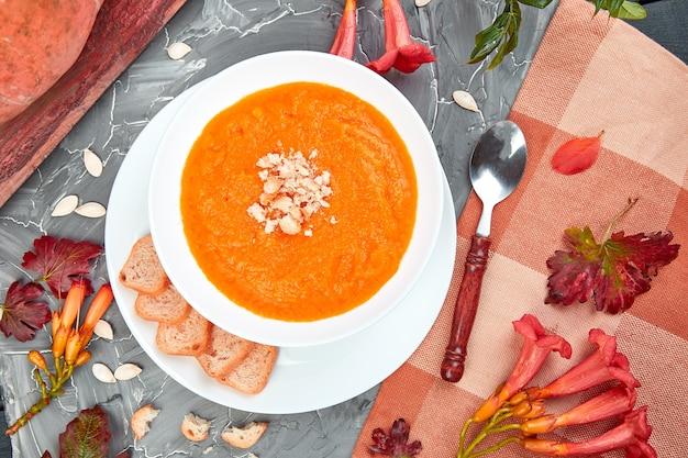 Cream of pumpkin soup on a gray background. diet vegetarian pupmkin soup