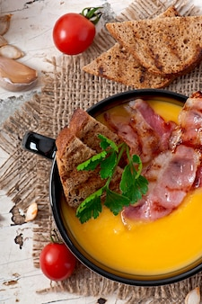 Cream of pumpkin soup with bacon and croutons