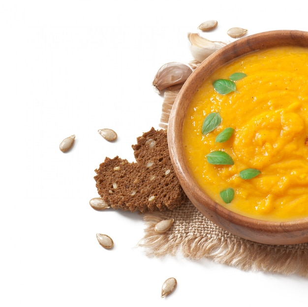 Cream of pumpkin soup in a wooden bowl