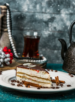 Cream sandwich cake covered in chocholate decorated with cinnamon sticks and coffee