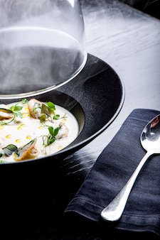 Cream soup is steaming in a black plate with on the black table.  for menu
