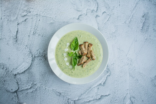 Cream soup made from mashed potatoes with zucchini and basil and crackers