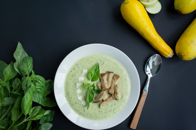 Cream soup of mashed potatoes with zucchini and basil and crackers