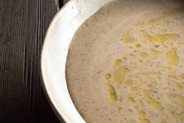 パンチップスのクローズアップと木製のテーブルの上のシャンピニオンのクリームスープ
