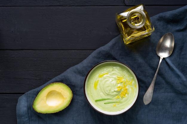 Крем-суп из огурцов и авокадо с цедрой лимона и оливковым маслом на черном фоне. вид сверху. горизонтальная ориентация.