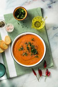 テーブルの上のトマトと赤レンズ豆のクリームスープ。家族全員のための健康なビーガン温暖化食品