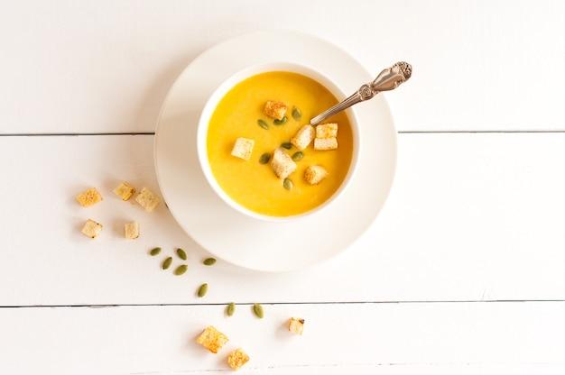 흰색 나무 테이블에 그릇에 croutons와 익은 호박의 크림 수프. 평면도.