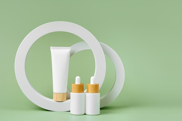 Cream tube and dropper mockup with  geometrical forms on green background