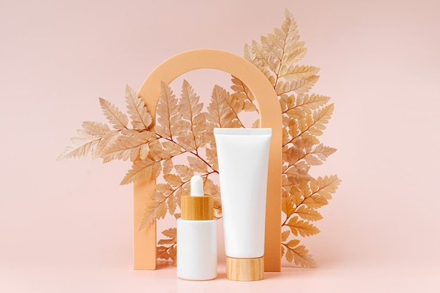 Cream tube and dropper mockup with leaf and geometrical forms on beige, background