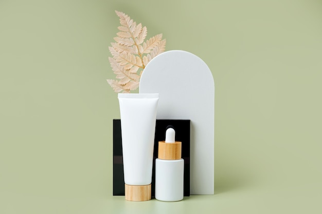 Cream tube and dropper mockup with leaf and geometrical forms on green background