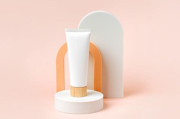 Cream tube  mockup on podium with  arch on  beige  background