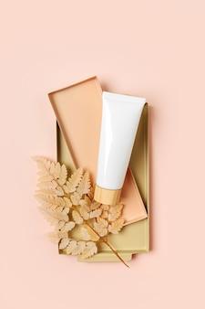 Cream tube mockup with beige leaf on pastel background