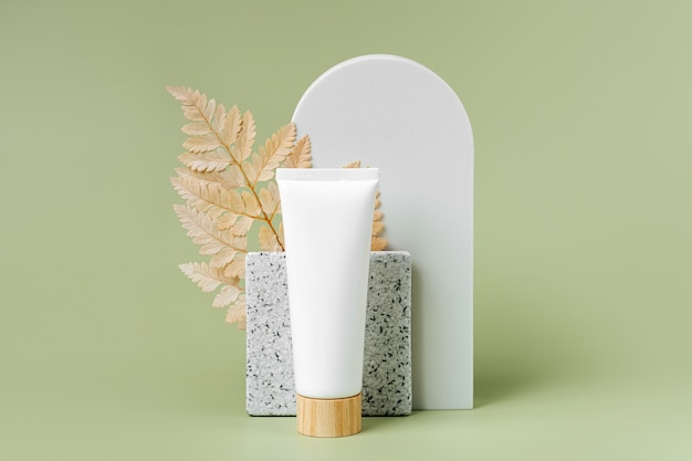 Cream tube  mockup with leaf and geometrical forms on green background