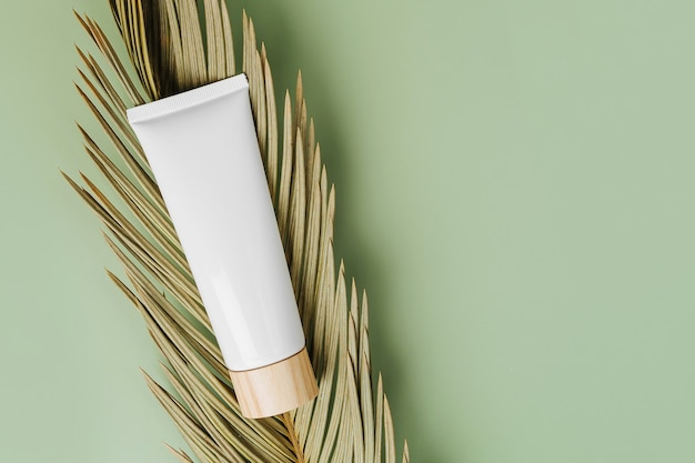 Cream tube mockup with palm leaf on green background