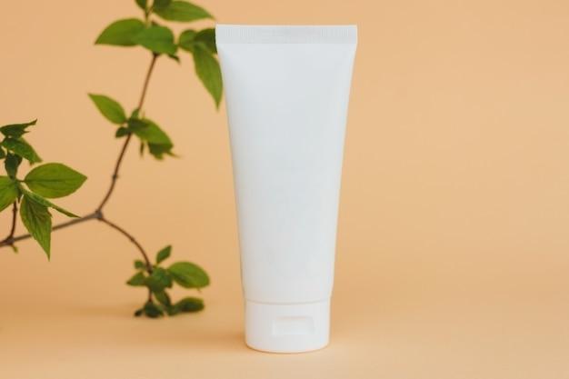 베이지 색 배경 화장품 스킨 케어 제품 빈 플라스틱 패키지에 크림 튜브 흰색 브랜드가없는 로션 발삼 핸드 크림 치약 모형